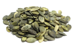 a handful of pumpkin seeds on a white background